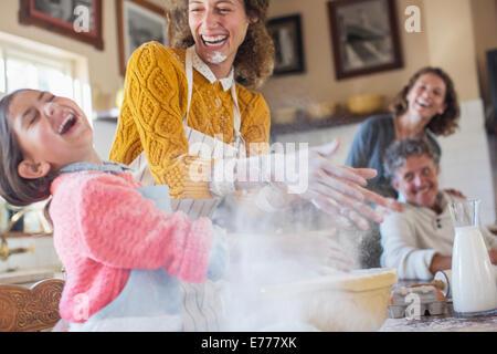 Madre e figlia giocando con la farina in cucina Foto Stock
