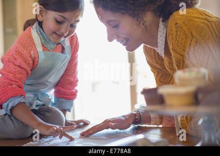 Madre e figlia giocando in farina insieme Foto Stock