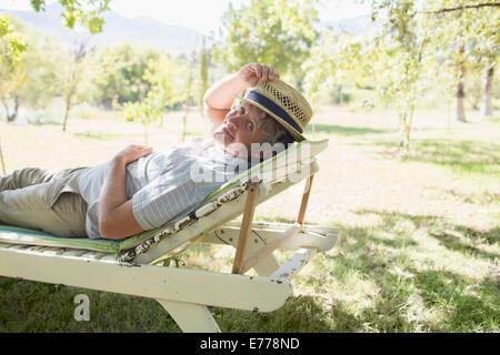 Uomo anziano rilassarsi sul prato sedia all'aperto Foto Stock