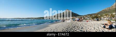 Vista panoramica di persone sulla spiaggia di Camps Bay, testa di leone in background, Cape Town, Sud Africa Foto Stock