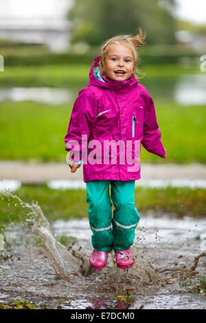 Felice bambina gioca in una pozza Foto Stock