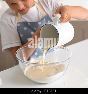 Ragazzo giovane 6-7 anni versando il latte in farina per fare la pastella per i pancake