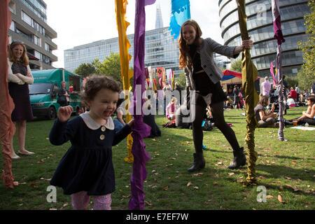 Gente radunarsi per appendere fuori, ascoltare le bande e altre attività presso la Blue Ribbon Village. Thames Festival Londra UK.