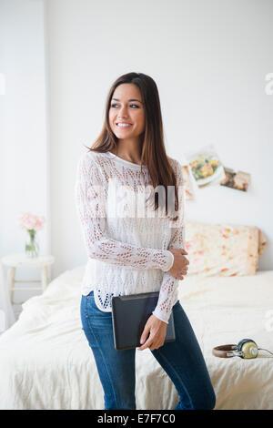 Donna che mantiene laptop in camera da letto Foto Stock