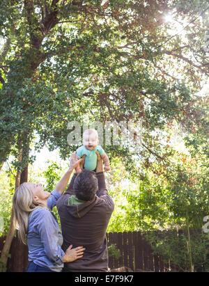 Coppia caucasica giocando con il bambino nel cortile posteriore Foto Stock