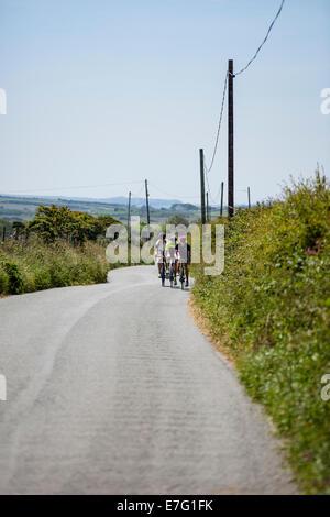 Tre i ciclisti cavalcare lungo un percorso attraverso la campagna del Pembrokeshire, Galles Foto Stock