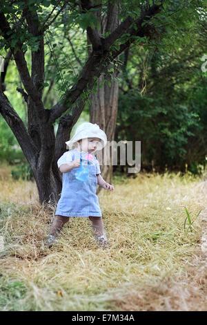 Il bambino in piedi.La bambina a piedi, prendendo i primi passi, emotivamente apprende il mondo. Foto Stock