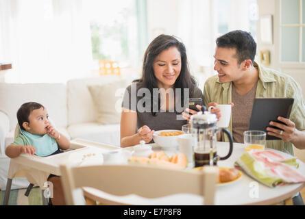 Famiglia con bambino figlio (6-11 mesi) in sala da pranzo Foto Stock