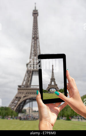 Giovane ragazza in viaggio e preso le immagini della Torre Eiffel, con la compressa Foto Stock