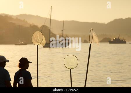 I pescatori con reti circolari stagliano contro la baia di Zihuatanejo, Guerrero, Messico. Foto Stock