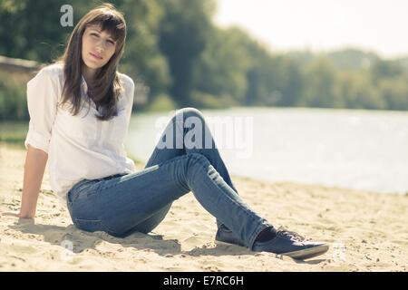 Giovane bella ragazza tanga in appoggio sulla spiaggia. Caucasian donna seduta sulla sabbia vicino all'acqua. Foto Stock