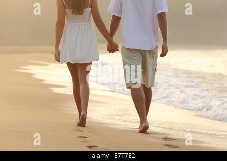 Vista posteriore di una giovane una passeggiata a piedi tenendo le mani sulla spiaggia di sunrise Foto Stock
