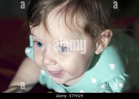 Bambina si posa sul suo stomaco su un arancione coperta. Lei è sempre sorridente e la sua lingua è un po'. Foto Stock