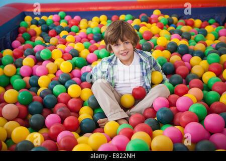 Carino ragazzo sorridente in piscina di palline Foto Stock