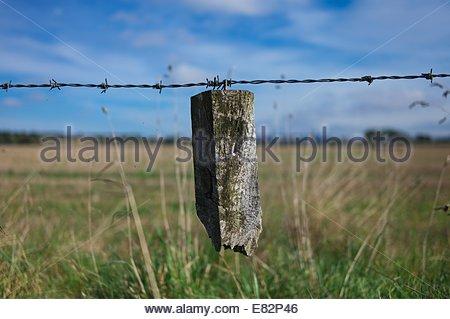 La rottura di un palo da recinzione pende dal filo spinato sul bordo di un campo di stoppie in Scottish Borders. Foto Stock