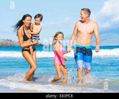 Felice razza mista famiglia di quattro persone di giocare e divertirsi in spiaggia Foto Stock
