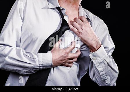 L'uomo pollice in su con una mano stretto al suo cuore area e rip off sua maglietta. Egli ha un attacco di cuore.