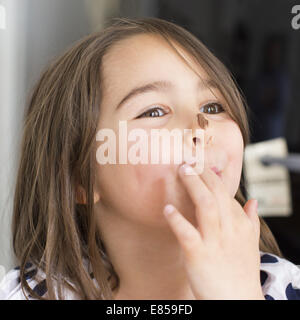 Ragazza con cioccolato cosparsa sul naso, leccarsi le dita Foto Stock
