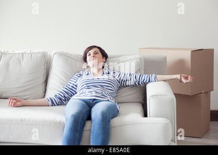 Donna appoggiata sul divano mentre casa in movimento Foto Stock