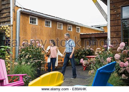 Coppia sorridente tenendo le mani sul patio cafe Foto Stock