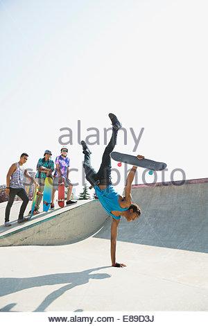 Ragazzo adolescente con lo skateboard facendo handstand Foto Stock