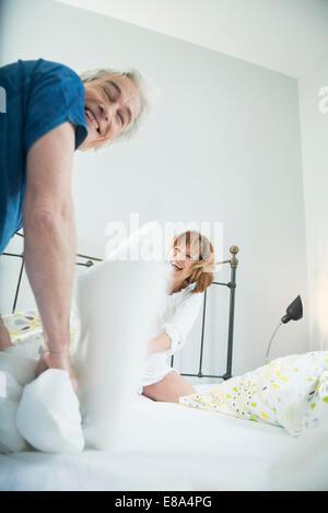 Paio di lotta di cuscini sul letto, sorridente Foto Stock