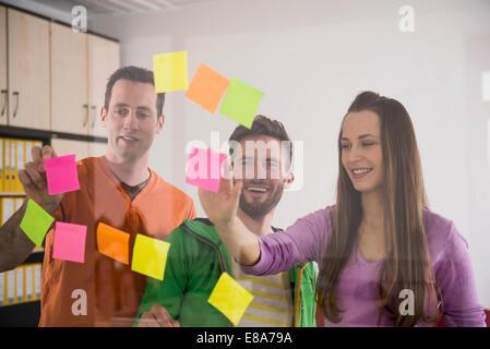 Giovani colleghi di pensare la pianificazione utilizzando dei post-it Foto Stock
