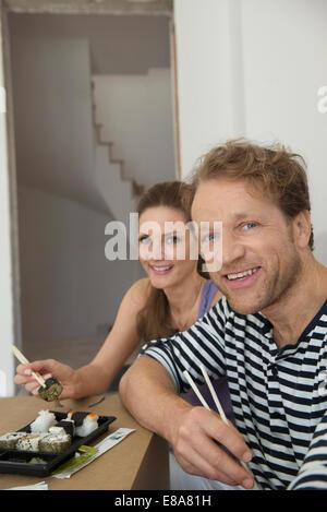 Ritratto giovane pranzo in appoggio a mangiare il sushi Foto Stock