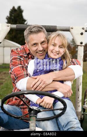 Agricoltore abbracciando la figlia sul trattore Foto Stock
