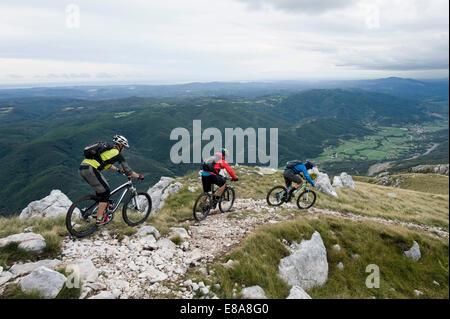 Tre i ciclisti di montagna cercando in vista della valle del Vipava, Istria, Nano, Slovenia Foto Stock