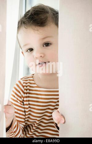 Ritratto di ragazzo giocando con tendina Foto Stock