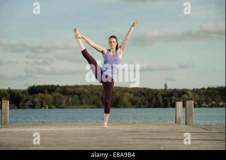 La donna a praticare yoga sul molo, Woerthsee, Baviera, Germania Foto Stock