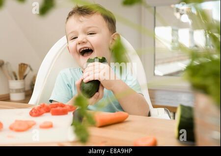 Ragazzo di mangiare cetriolo in cucina, sorridente Foto Stock