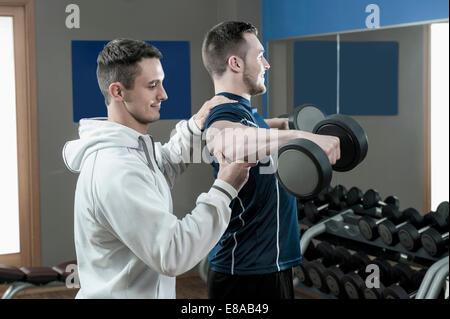 Coach sostenendo l uomo in palestra facendo il peso della formazione Foto Stock
