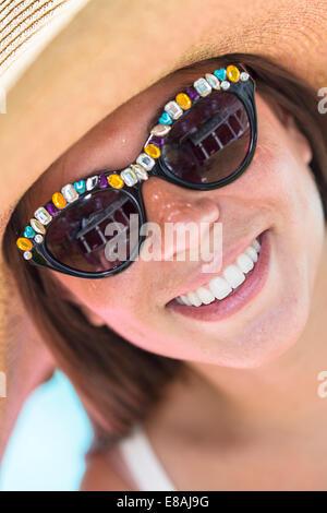 Close up ritratto di giovane donna che indossa gli occhiali da sole e cappello Foto Stock