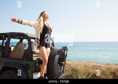 Giovane donna in piedi sul retro della jeep a costa con le braccia aperte, Malibu, California, Stati Uniti d'America Foto Stock