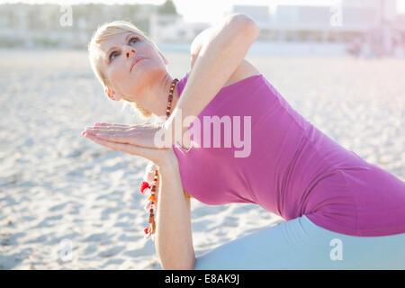 Donna in preghiera yoga pone sulla spiaggia