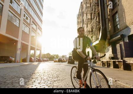Messenger maschio in bicicletta lungo una strada di città Foto Stock