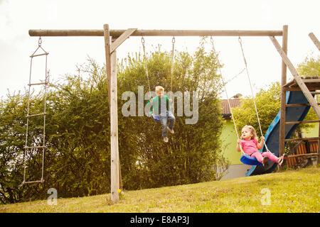 Fratello e Sorella gioca su altalene in giardino Foto Stock