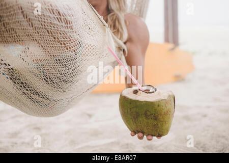 L'uomo godendo di acqua di cocco in amaca sulla spiaggia Foto Stock