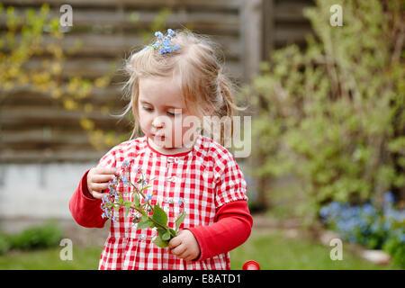 Ragazza giovane indossando abiti gingham holding fiori Foto Stock