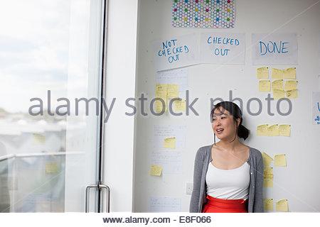 Imprenditrice sorridente con di fronte la lavagna con note adesive Foto Stock