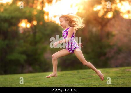 Stati Uniti d'America, bambina (8-9) indossando il costume da bagno il salto nel cortile posteriore Foto Stock