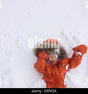 Felice ragazzo che giace sulla neve, Lake Tahoe, California, USA Foto Stock