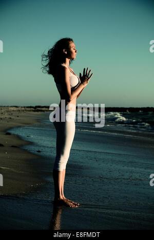 Vista laterale della donna in piedi sulla spiaggia a praticare lo yoga con le mani in posizione di preghiera Foto Stock
