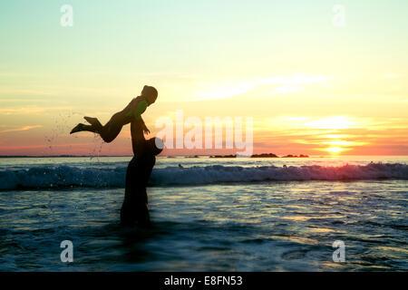 Sud Africa, Western Cape, Cape Town, Silhouette di padre e figlia (4-5) sulla spiaggia al tramonto Foto Stock