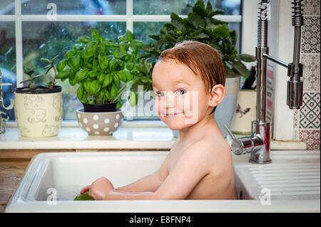 Ragazzo (2-3) tenendo bagno nel lavello da cucina Foto Stock