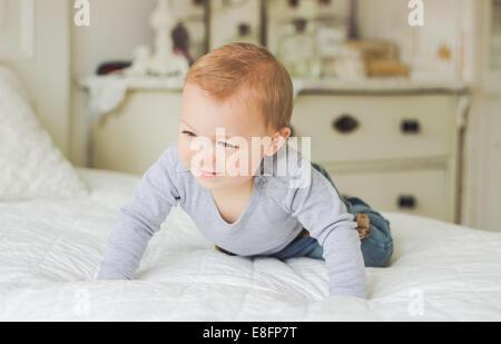 Baby strisciando sul letto Foto Stock