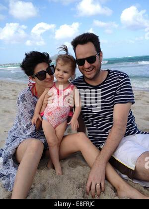 Madre, padre e figlia (18-23 mesi) seduto sulla spiaggia Foto Stock