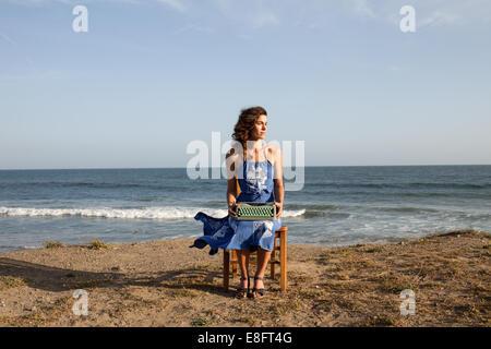 Donna seduta su una sedia sulla spiaggia con una macchina da scrivere Foto Stock